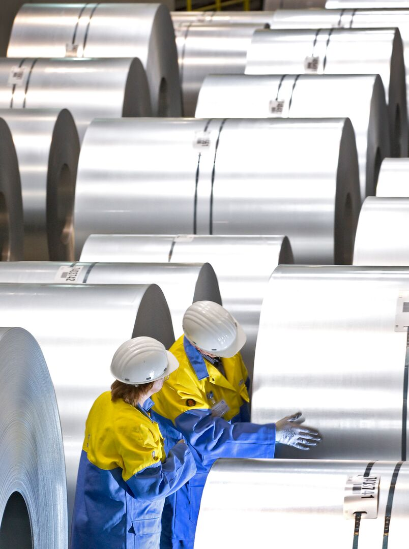 Tata Steel employees in protective gear checking tinplate coils