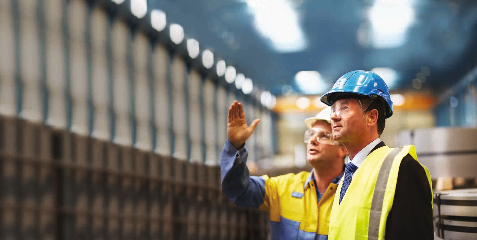 Tata Steel employees in a manufacturing environment wearing protective equipment