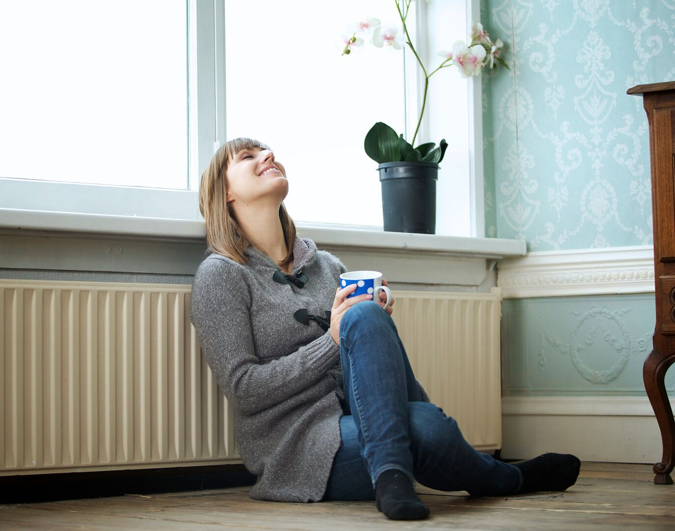 Lady sitting on the floor leaning back on a radiator